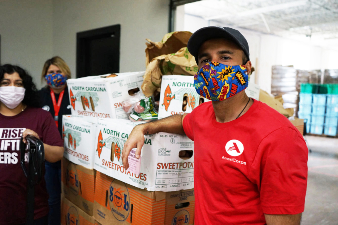 Man wearing a face mask standing next to crates of food