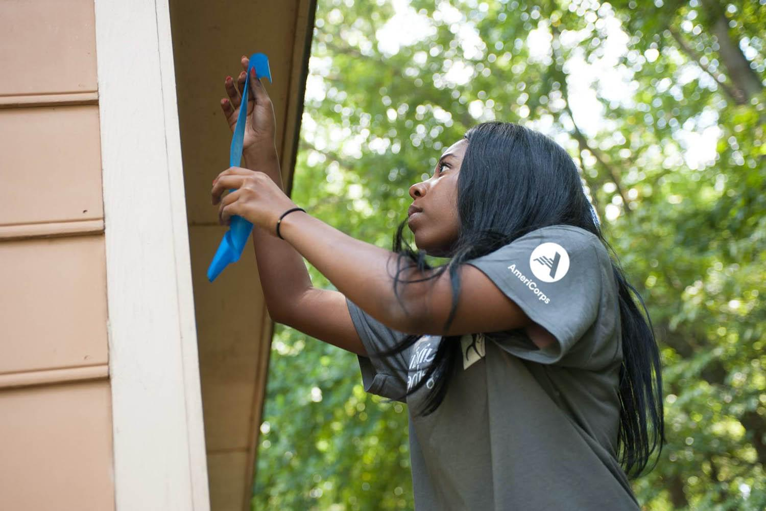 Woman wearing an AmeriCorps T-shirt hammering