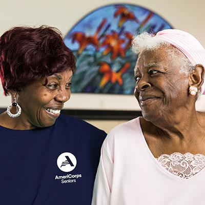 Two women looking at each other one wearing an AmeriCorps Seniors top