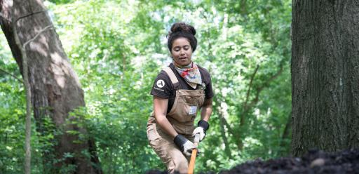 Woman wearing an AmeriCorps T-shirt working in a wooded area