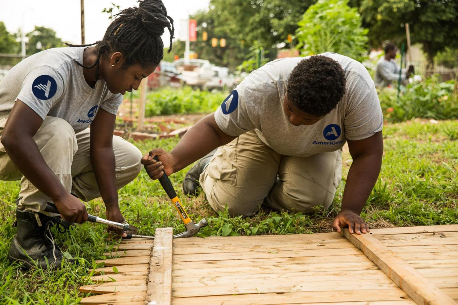 Two women wearing AmeriCorps T-shirts building a fence