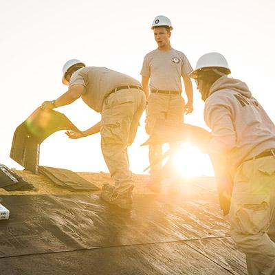 Three people laying tiles on a roof