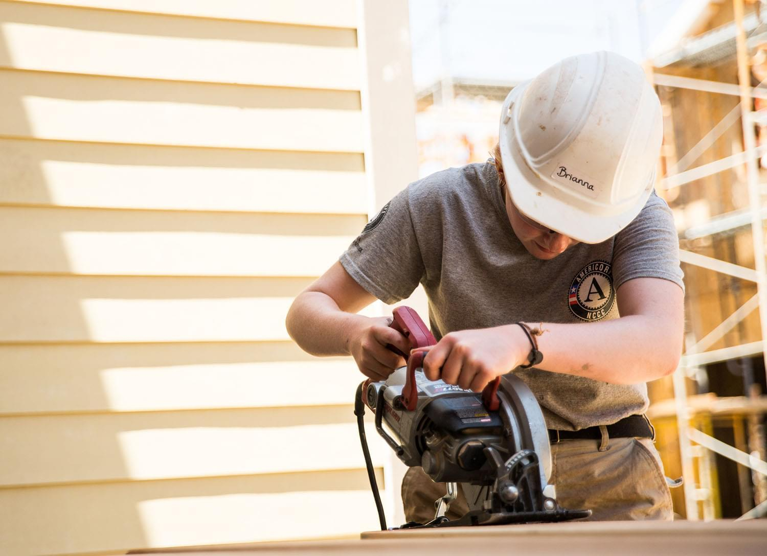 Woman wearing a hard hat using an electric sander