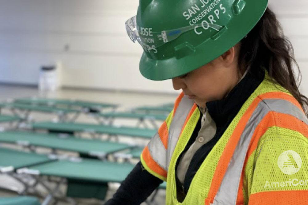 Woman wearing a green hard hat and an AmeriCorps high vis jacket