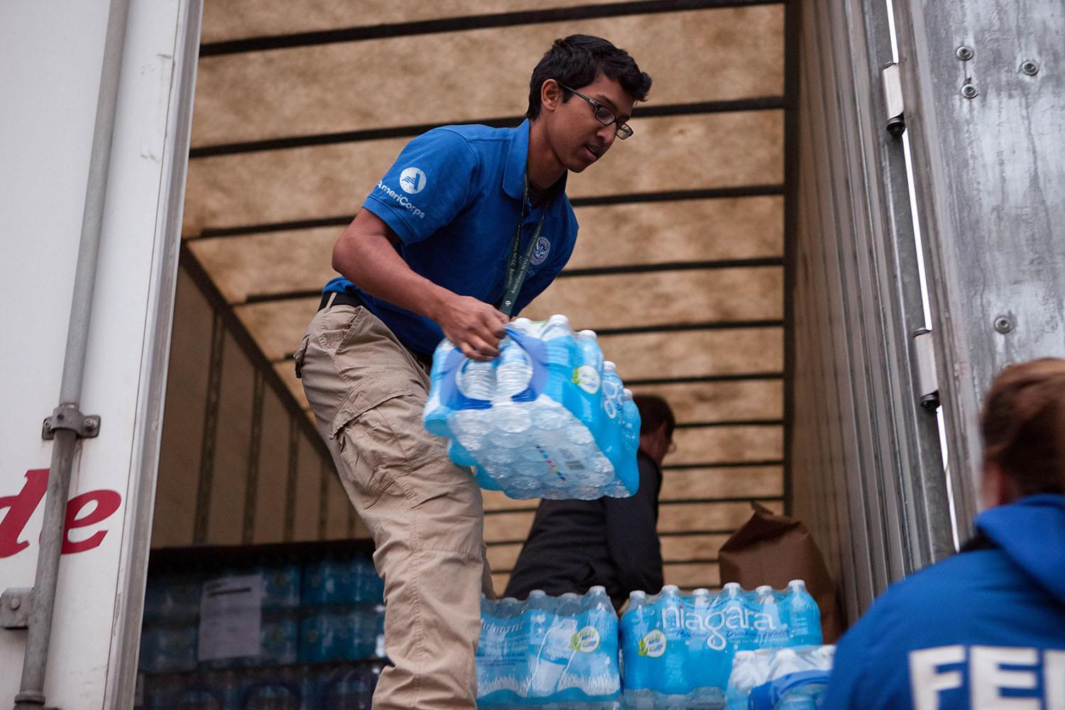 Man passing a pack of water bottles out of a truck