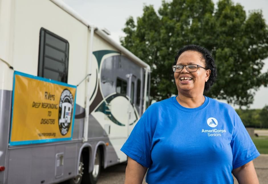 Woman wearing an AmeriCorps Seniors T-shirt standing in front of an RV