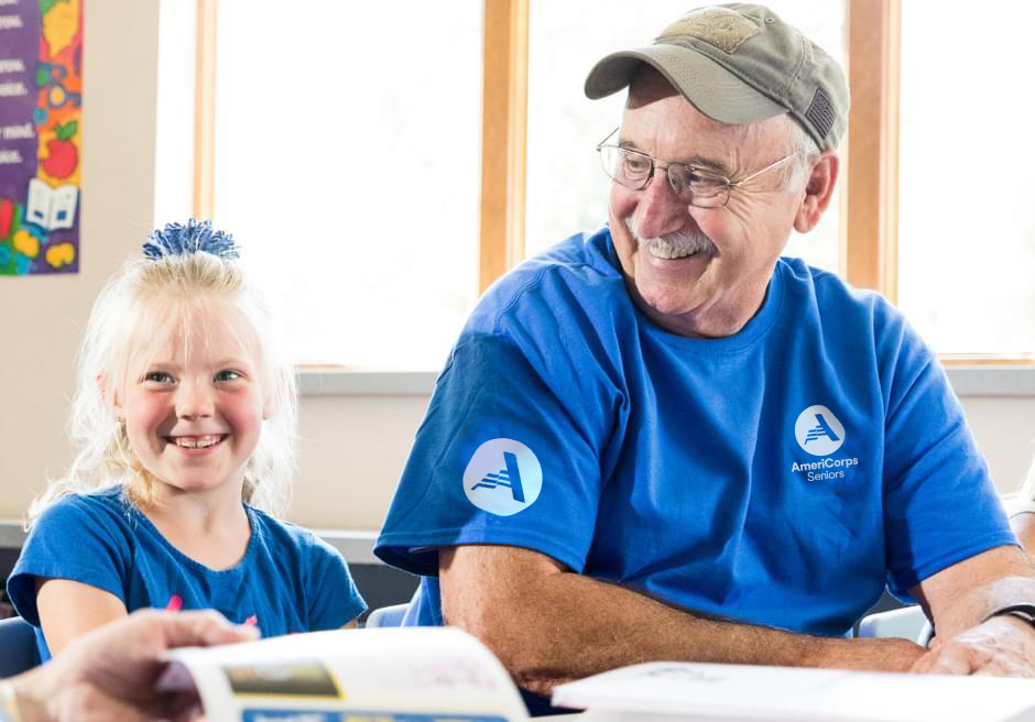 A man wearing an AmeriCorps Seniors T-shirt sitting next to a smiling little girl
