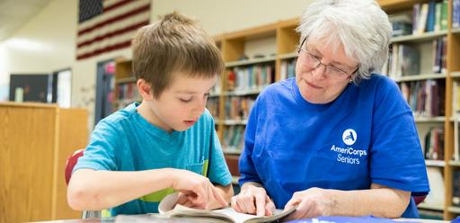 Lady wearing an AmeriCorps T-shirt reading with a small boy